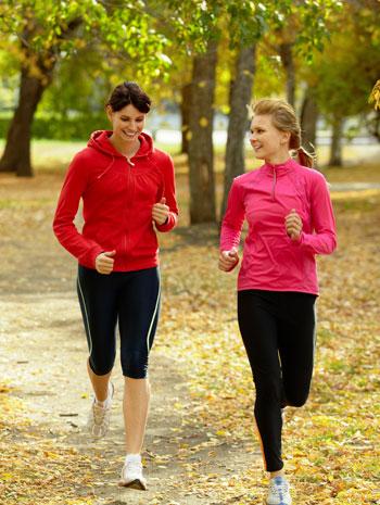 women jogging on dirt path through park