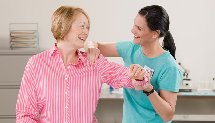physical therapist working with ladys shoulder