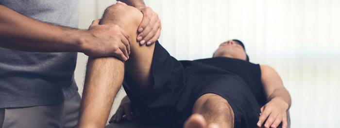 physical therapist working with patients knee