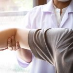 physical therapist working with patients shoulder