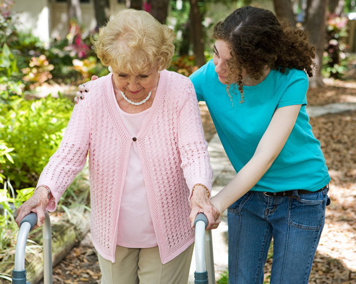 young woman helping elderly lady with walker
