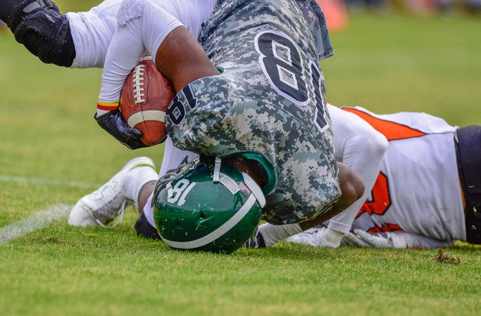 highschool football players tackling