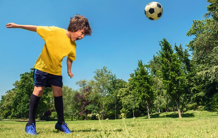 young boy hitting soccer ball with head