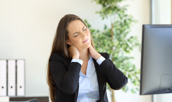 woman at work desk cracking her neck