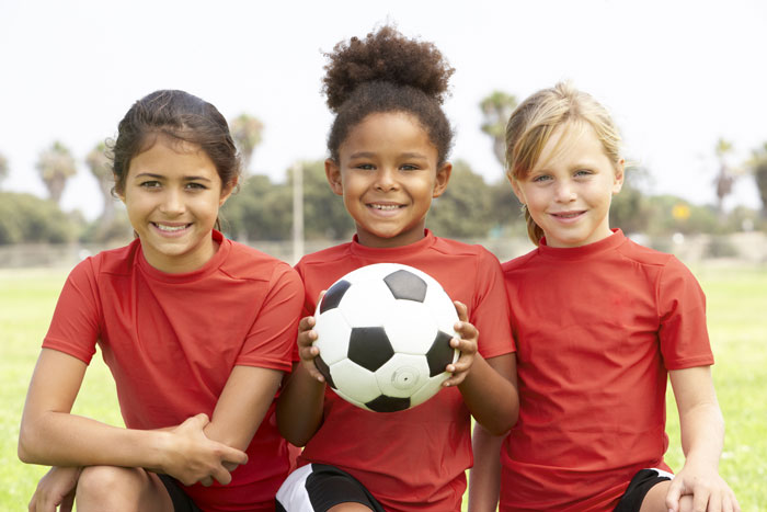 happy young girl soccer players with ball