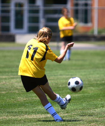 preteen girl kicking the soccer ball