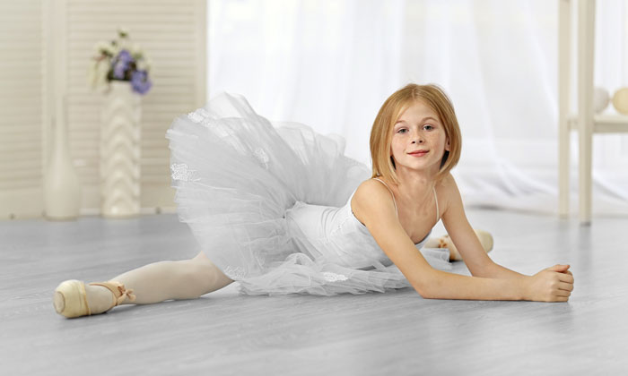 young ballet dancer girl stretching on floor