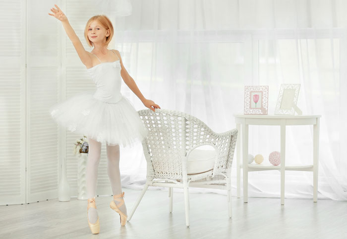 young ballet dancer standing holding onto chair