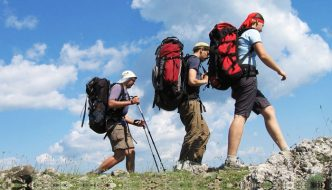 three backpackers hiking mountain