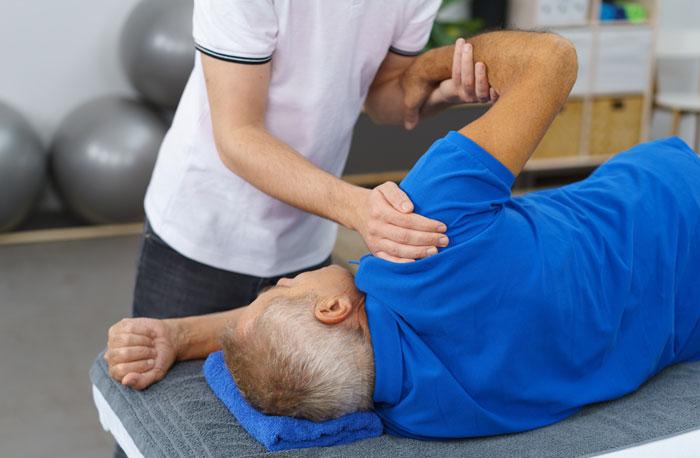 therapist working with patients healing shoulder