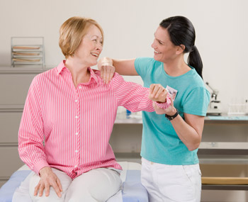 therapist helping lady with hurting shoulder