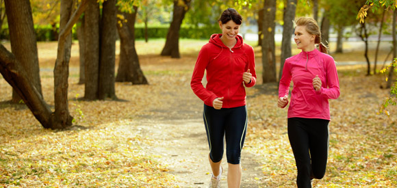two women running through park